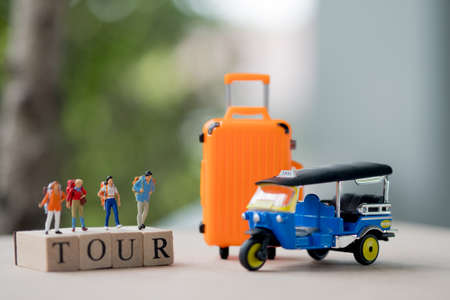 Group miniature traveler and hiker backpack standing on wooden text TOUR with suitcase for the tourist and adventure Standard-Bild