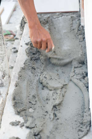 Hands of manual worker with plastering tools renovating house. Plasterer renovating outdoor floor and corners with spatula and plaster. Construction works