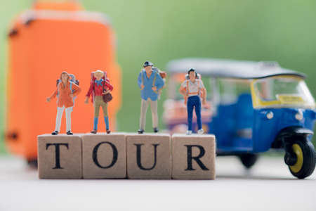 Miniature people : Traveler with backpack standing on wooden word TOUR with tuk-tuk and suitcase background