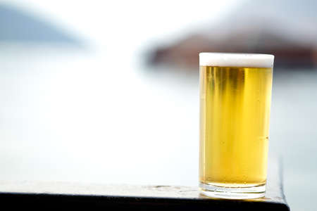 Fresh of beer in long glass on the table with nature background