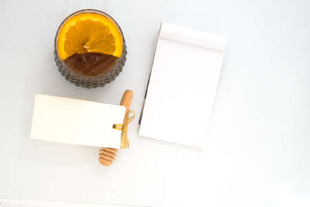 Iced americano with piece of orange, honey box and empty note on white background