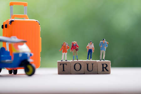 Miniature people : Traveler with backpack standing on wooden word TOUR with nature background, Concepts of travel and adventure in Thailand. Business travel concept Standard-Bild