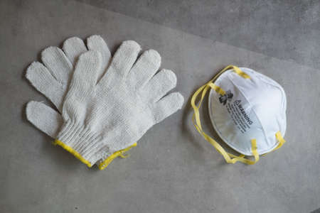 Protective mask respirator and gloves on cement background