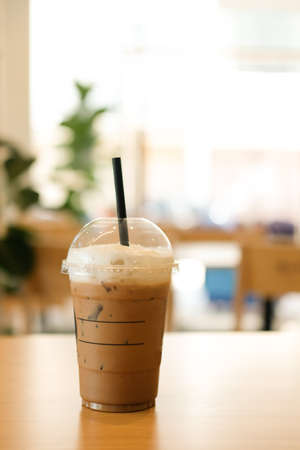 Iced mocha coffee in Take away glass on the table at coffee shop Foto de archivo
