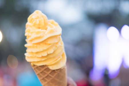 Melted ice cream flavor of passion fruit on a waffle cone