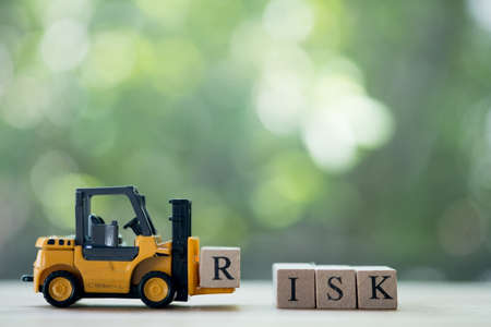 Toy forklift hold letter block R to complete word RISK. Concept of risk assessment for business or investment