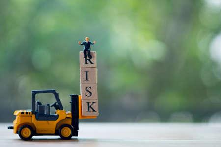Un homme d'affaires miniature assis au sommet d'une tour de blocs de bois instable avec des alphabets combine le mot RISK. Évaluation des risques pour les entreprises ou les investissements Banque d'images