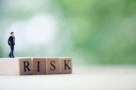 Miniature businessman walk on cube blocks letter RISK. Investment Risk management concept 写真素材