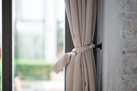 Part of beautifully draped curtain on the window in the room