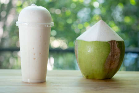 Coconut smoothie in plastic glass, homemade summer drink