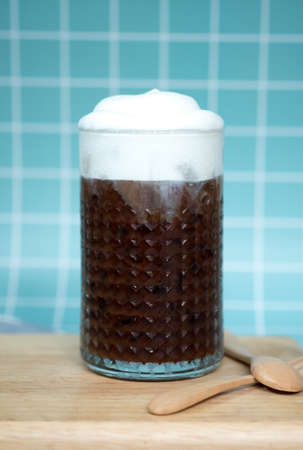 Iced mocha coffee with milk foam on top served on wooden tray