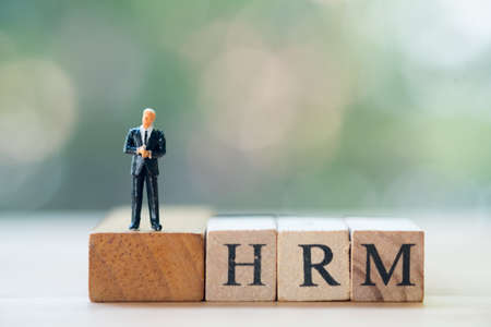 Miniature businessman standing on wooden block word HRM in concept of human resource management concepts. (Human resource management : HRM) Stock Photo