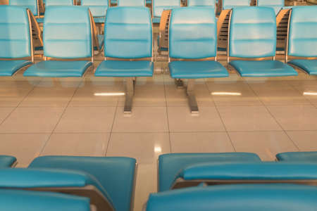 Blue bench in the terminal of airport with chairs, waiting area for passengers Imagens