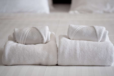 Stack of white bath towels on bed sheet in modern hotel bedroom interior Stock Photo
