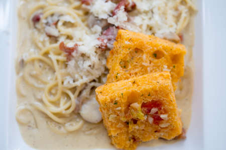 Spaghetti with carbonara sauce and bread, selective focus