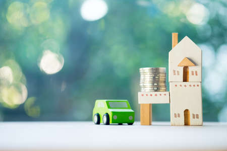 Close up of coins and toy home toy car on wooden table on blur background, saving money for car and home. Business concept