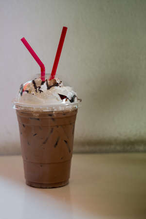 Iced cocoa with whipped cream and drinking straw in plastic cup Foto de archivo