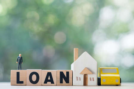 Miniature businessman stand on wood block words LOAN with wooden home and car. The concept of buying and selling real estate and car