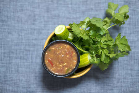 Spicy shrimp paste chilli sauce served with fresh cucumber and coriander, top view
