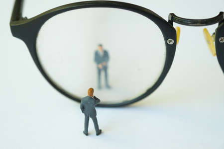 Miniature businessman standing looking through glasses, using as background business concept with copy space and white space. Stock Photo