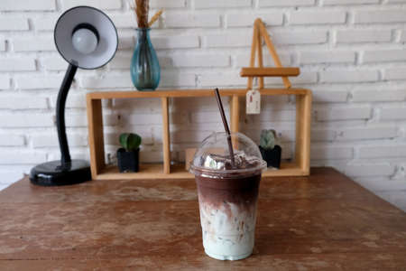 Iced chocolate or cacao with milk and mint syrup in glass on wood tabel at coffee shop