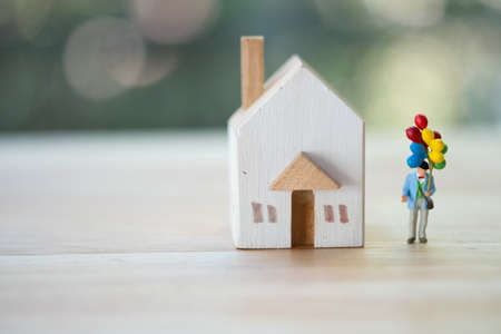 Miniature people : Old man holding colorful balloon next to home, concept of happy after retire