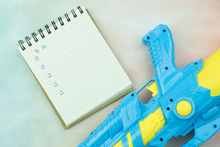Plastic water gun and notepad with a to do list in holiday, Songkran festival in Thailand