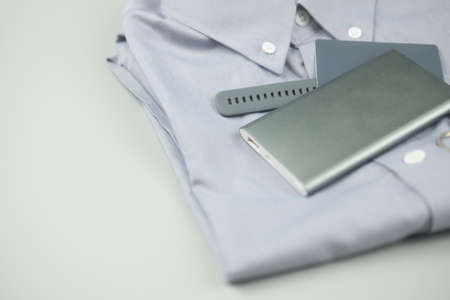 Gray colour clothing and electronic item gray colour (silver power bank, smart watch and credit card) on gray background