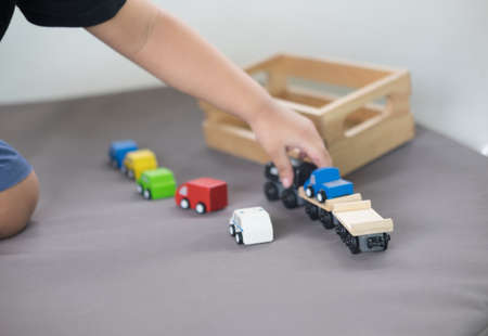 Little boy playing with a colourful wooden toy car on the carpet in the living room in the house 写真素材