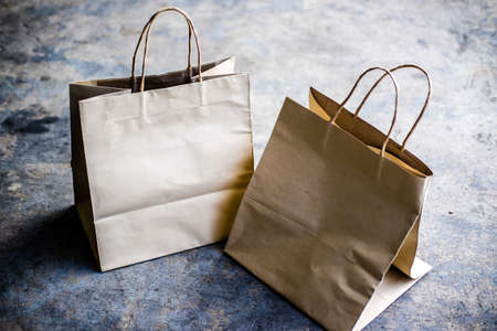 Kraft paper shopping bags on cement background