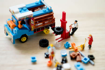 Miniature people : workers are preparing and fix farming Thai trucks. Image use for engine maintenance, car care. 写真素材