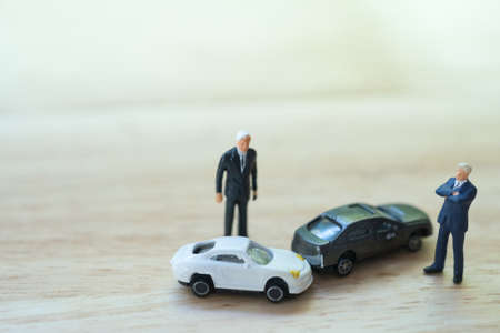 ミニチュアの人:自動車事故の衝突後に議論している2人のドライバーの男。交通事故と保険の概念。