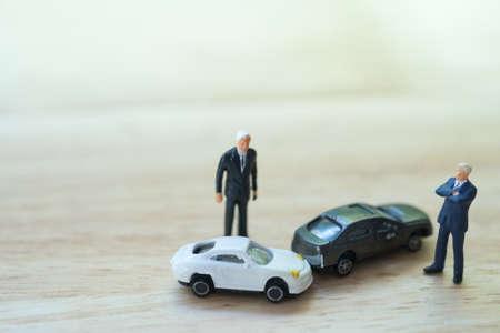 Miniaturleute: Zwei Fahrer streiten sich nach einer Kollision mit einem Autoverkehrsunfall. Verkehrsunfall- und Versicherungskonzept.