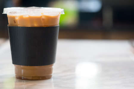 Iced coffee with black paper sleeve