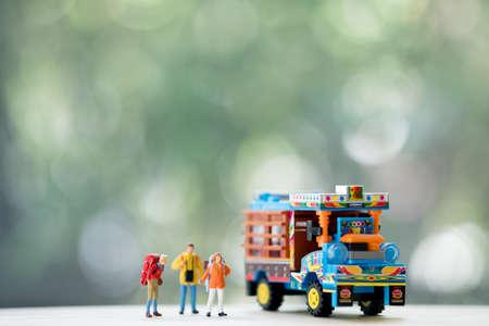 Gente en miniatura: viajero con mochila junto a camiones agrícolas tailandeses, conceptos de viajes y aventuras en Tailandia y concepto de autostop Foto de archivo