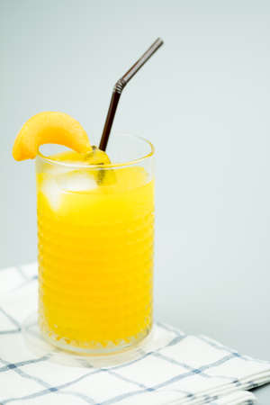 Freshly squeezed sweet orange juice with ice cubes and decoration with slice peach