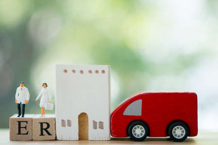 Miniature people: Doctor and nurse standing on wooden block with words ER, car and hospital. Concept of prepared emergency in long holiday Stock fotó