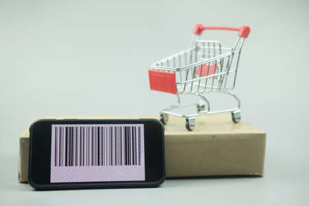 Smartphone with barcode on screen with shopping cart on brown box. Concept of online shopping, E commerce and delivery of goods.