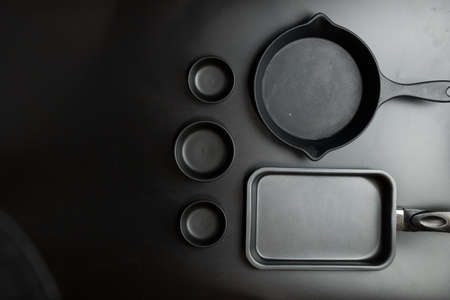 Different sizes black cook pan and black different sizes bowl on black table top. View from above.