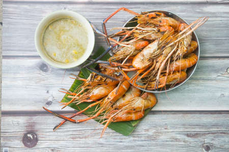 Grilled shrimp with spicy sauce on wood table