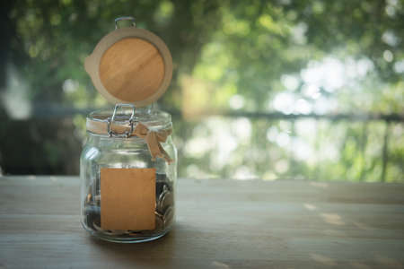 Thai baht in a glass jar on wood table with nature background. Saving concepts