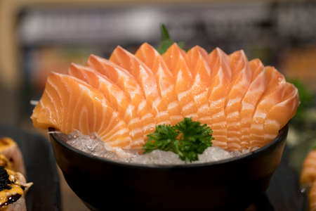 Japanese food sashimi salmon in black bowl decoration with vegetable on iced. Sashimi is something raw, sliced and served - most popular sashimi is seafood. Imagens