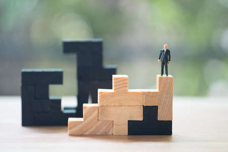 Miniature people: Businessman standing on puzzle pieces. Concept of leader different. Stok Fotoğraf