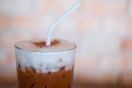 Glass of iced cocoa drink and milk froth cream foam