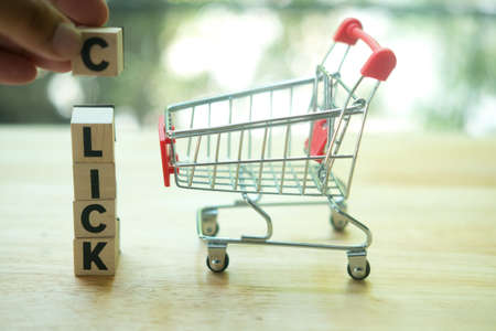 Small wooden word with the word Click on wood table, hand puts the c on it. Concept of shopping online