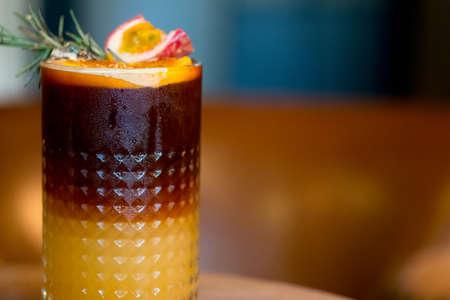 Iced Black Coffee Mix mit Maracujasaft und Orangensaft und Dekoration mit Orangenscheibe und Maracujascheibe. Sommer-Fusion-Drink Standard-Bild
