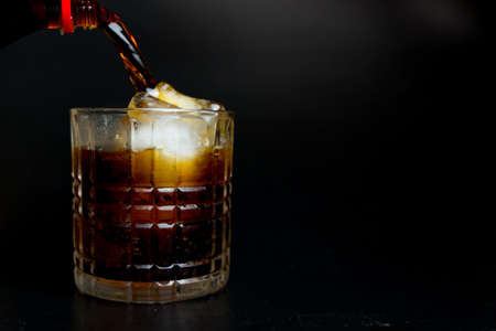 Soft drink pouring to glass with ice on dark background Stok Fotoğraf
