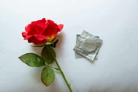 Condom and red rose on white pillow. Concept of birth Control Stock Photo