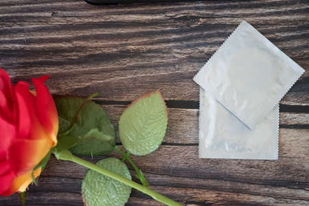 Close up with condom and red roses on wooden table. Valentine concept Stock Photo - 127691383