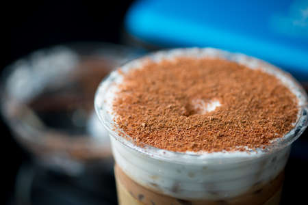 Iced coffee with classic tiramisu dessert on top. Fusion drink